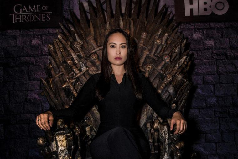 Modelo sentada no Trono de Ferro da série Game of Thrones